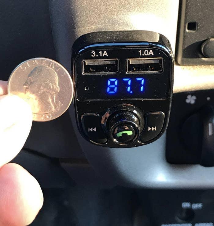 reviewer holding quarter next to bluetooth adapter