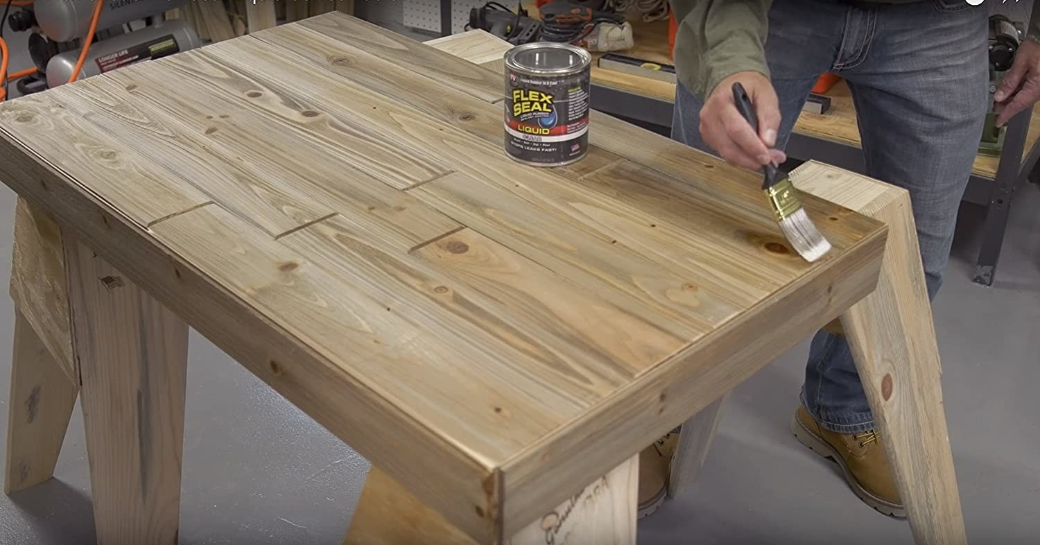 person painting flex seal onto a table