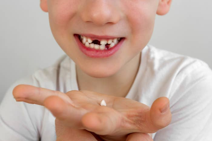 A child holding a tooth in their hand