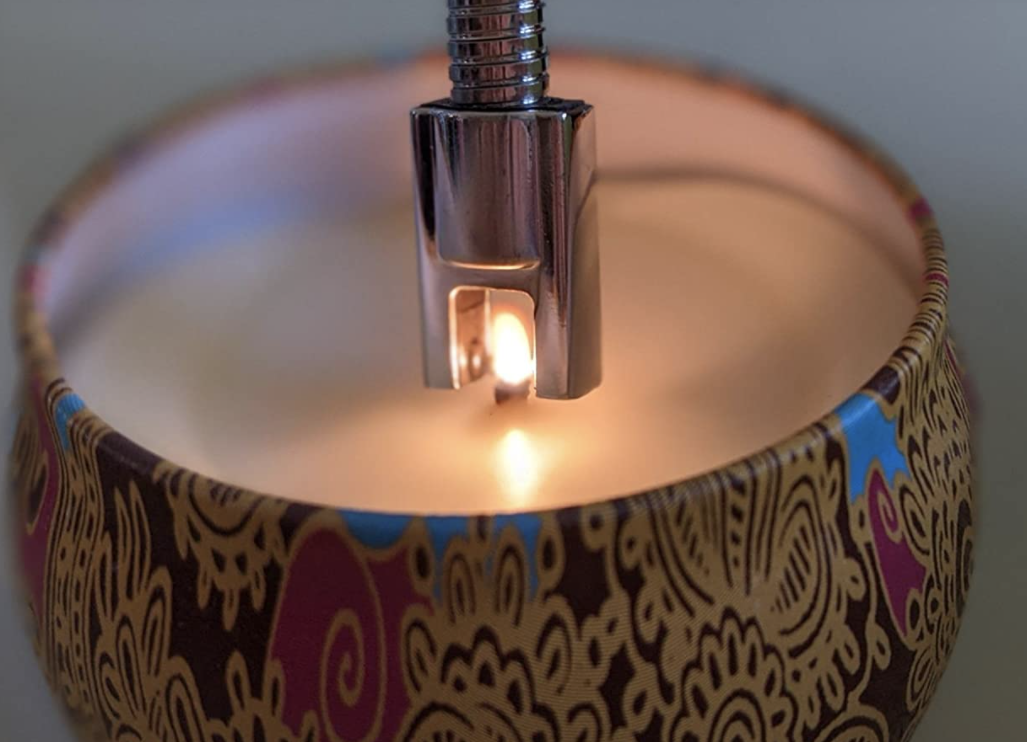 A reviewer lighting a candle with the tool
