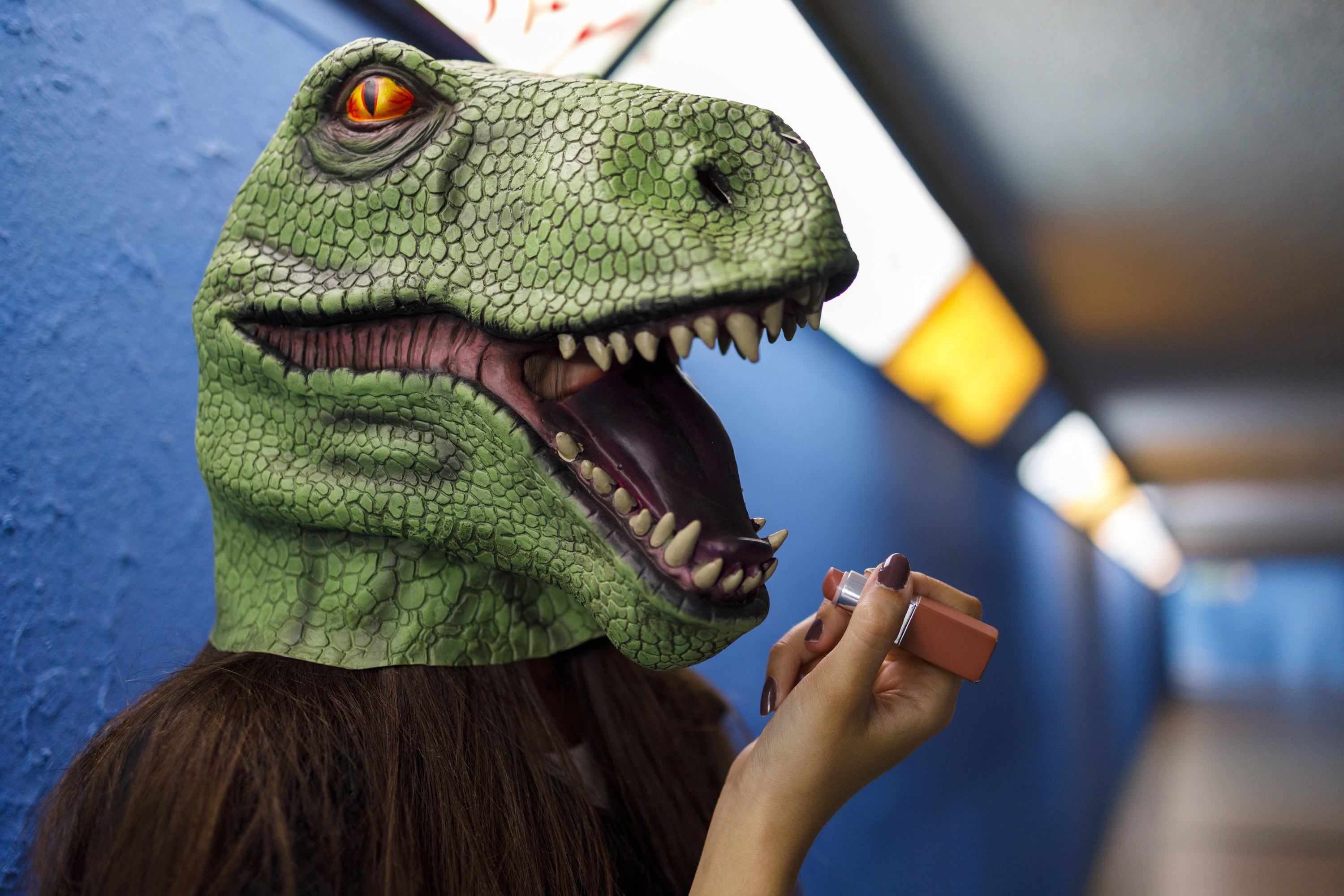 Someone wearing a dinosaur head and holding up a tube of lipstick to their lips