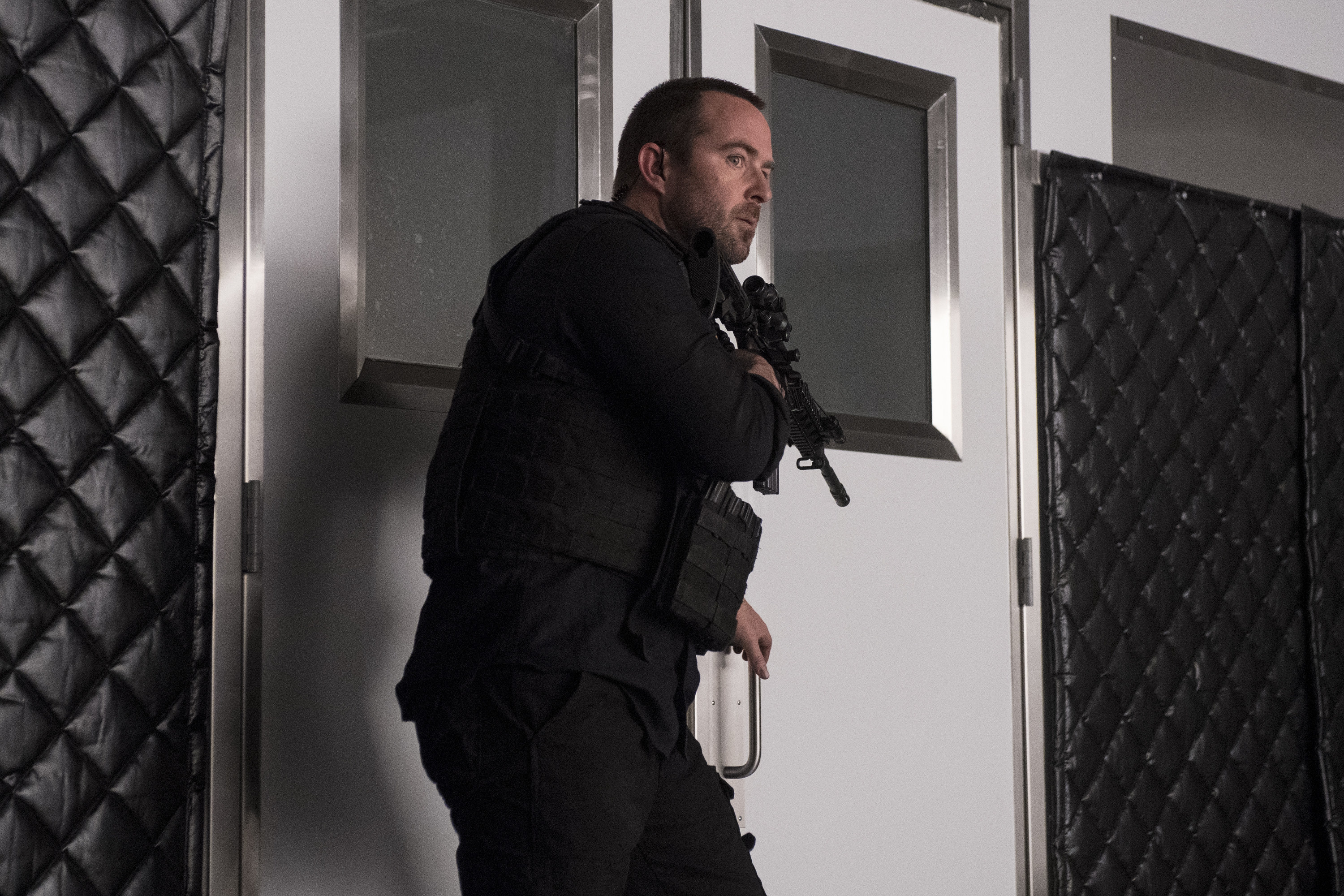 A man holding a gun and wearing a bullet proof vest