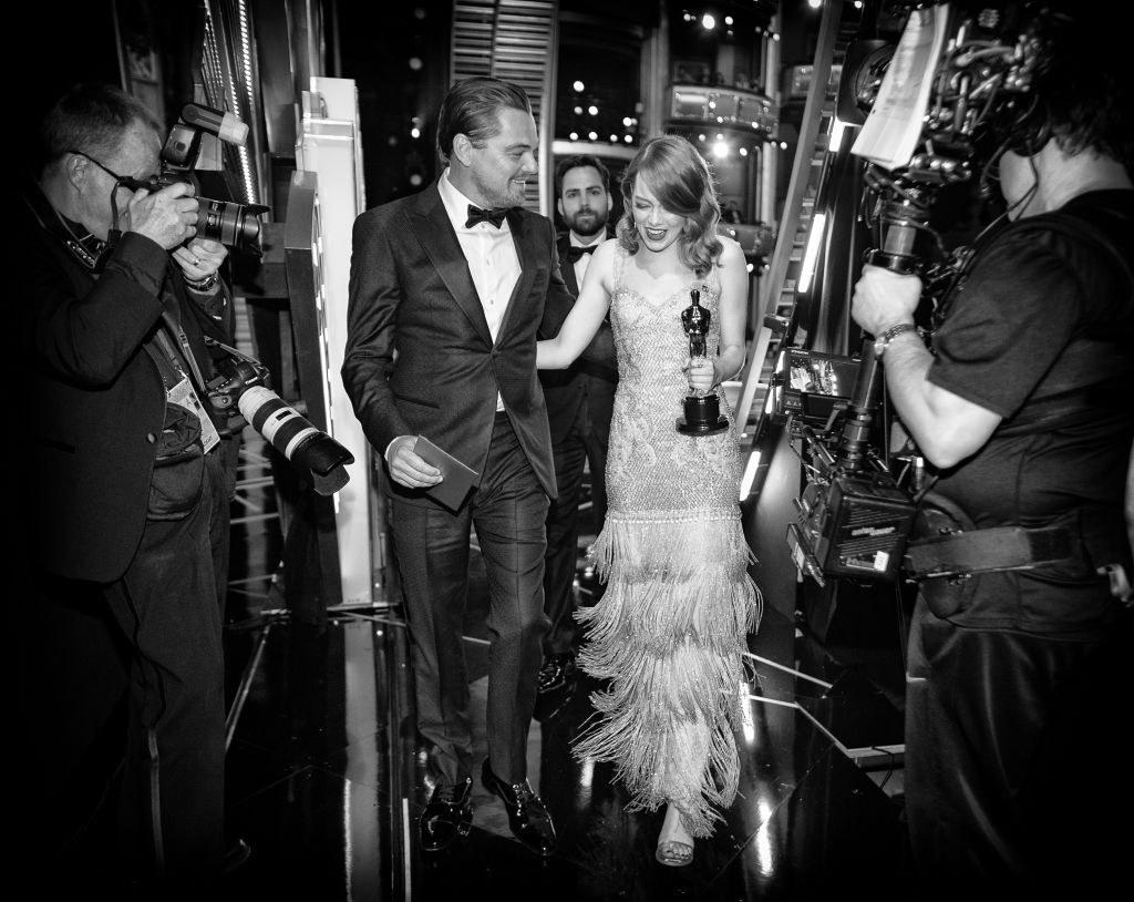 Black and white photo of Leonardo DiCaprio and Emma Stone walking backstage at the 2017 Oscars