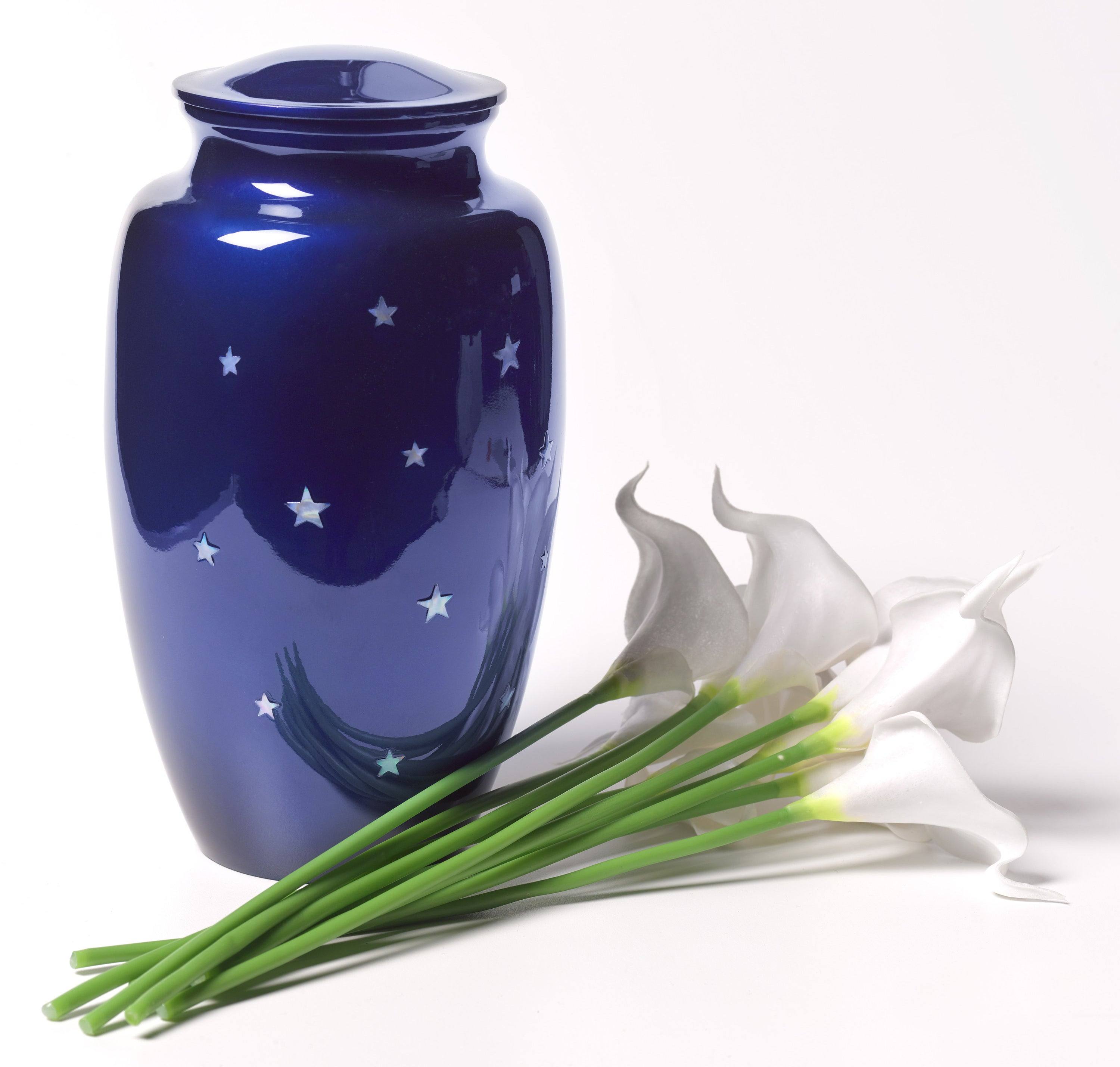 An urn next to several flowers