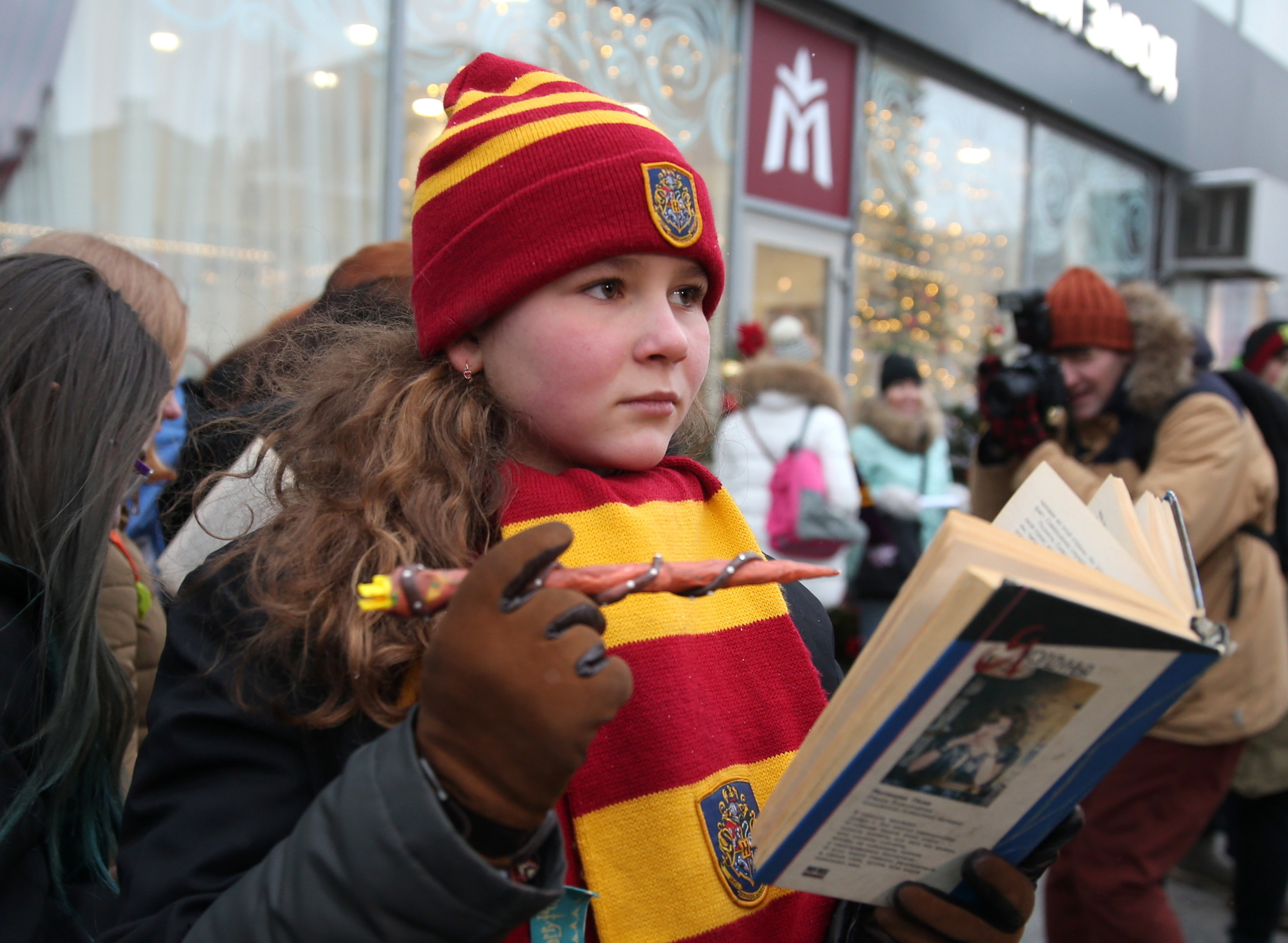 A child wearing a Gryffindor knit cap and scarf and holding a wand