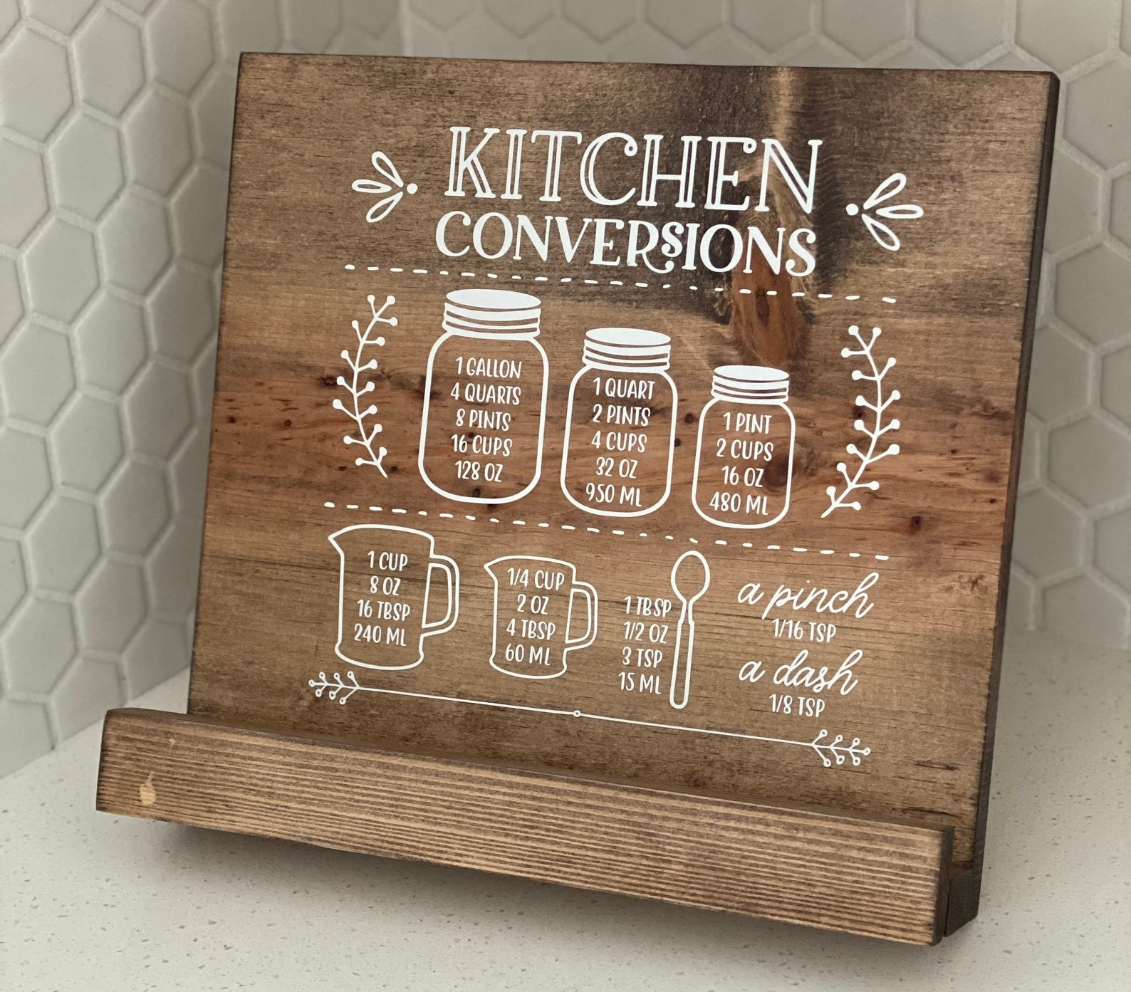 a dark wooden cookbook holder with a white hand-painted kitchen conversions design