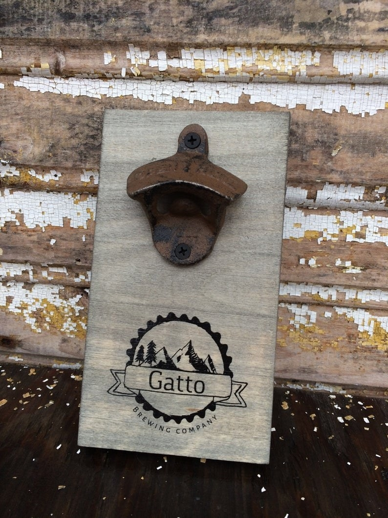 """slate gray wooden sign with a bottle opener on top and a black etched logo that says """"gatto brewing company"""" on bottom"""