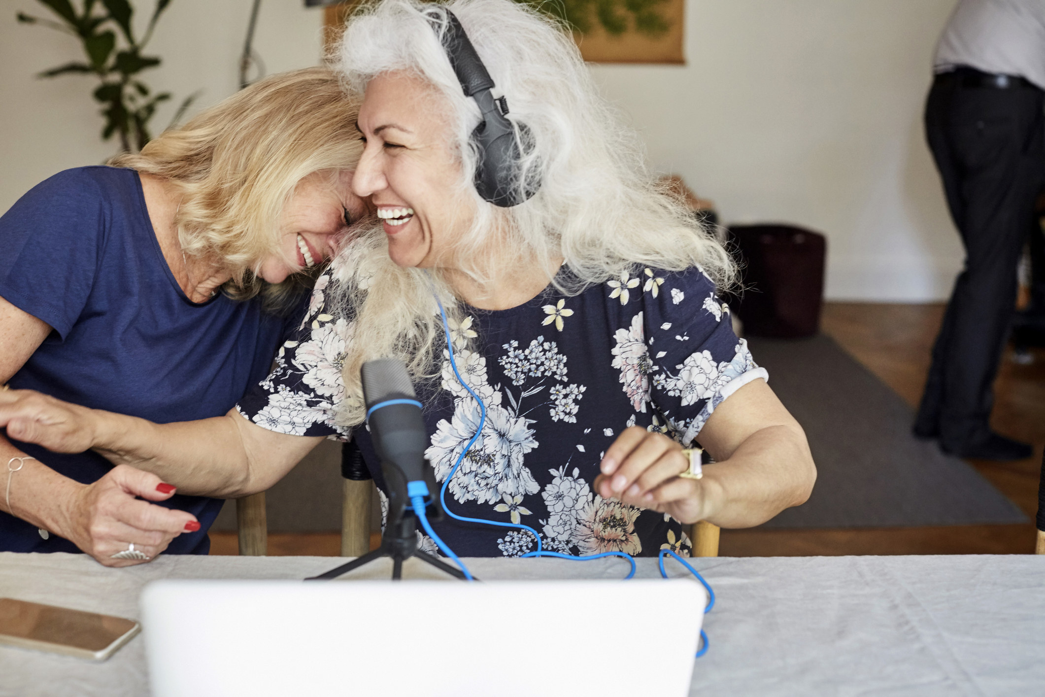 An older woman recording audiobooks with a mic and a laptop