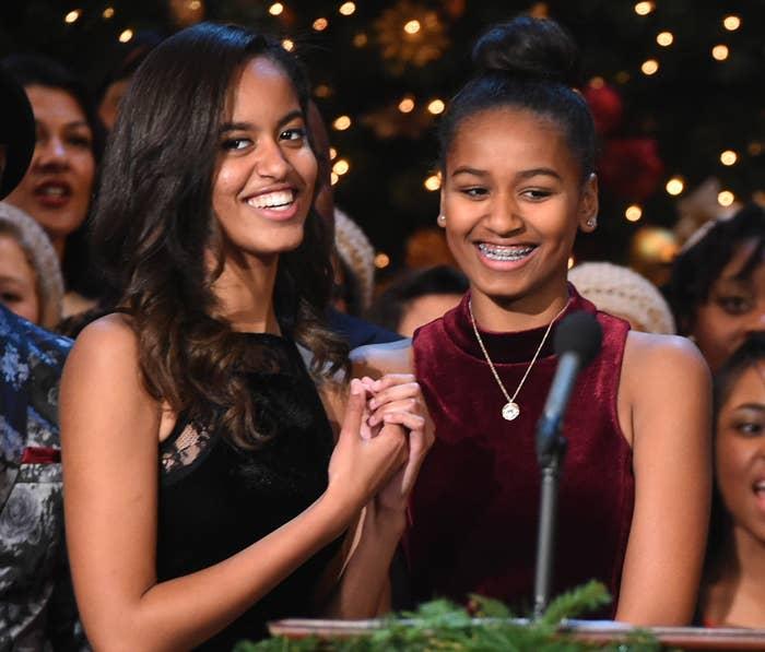 Malia and Sasha smile onstage at an event