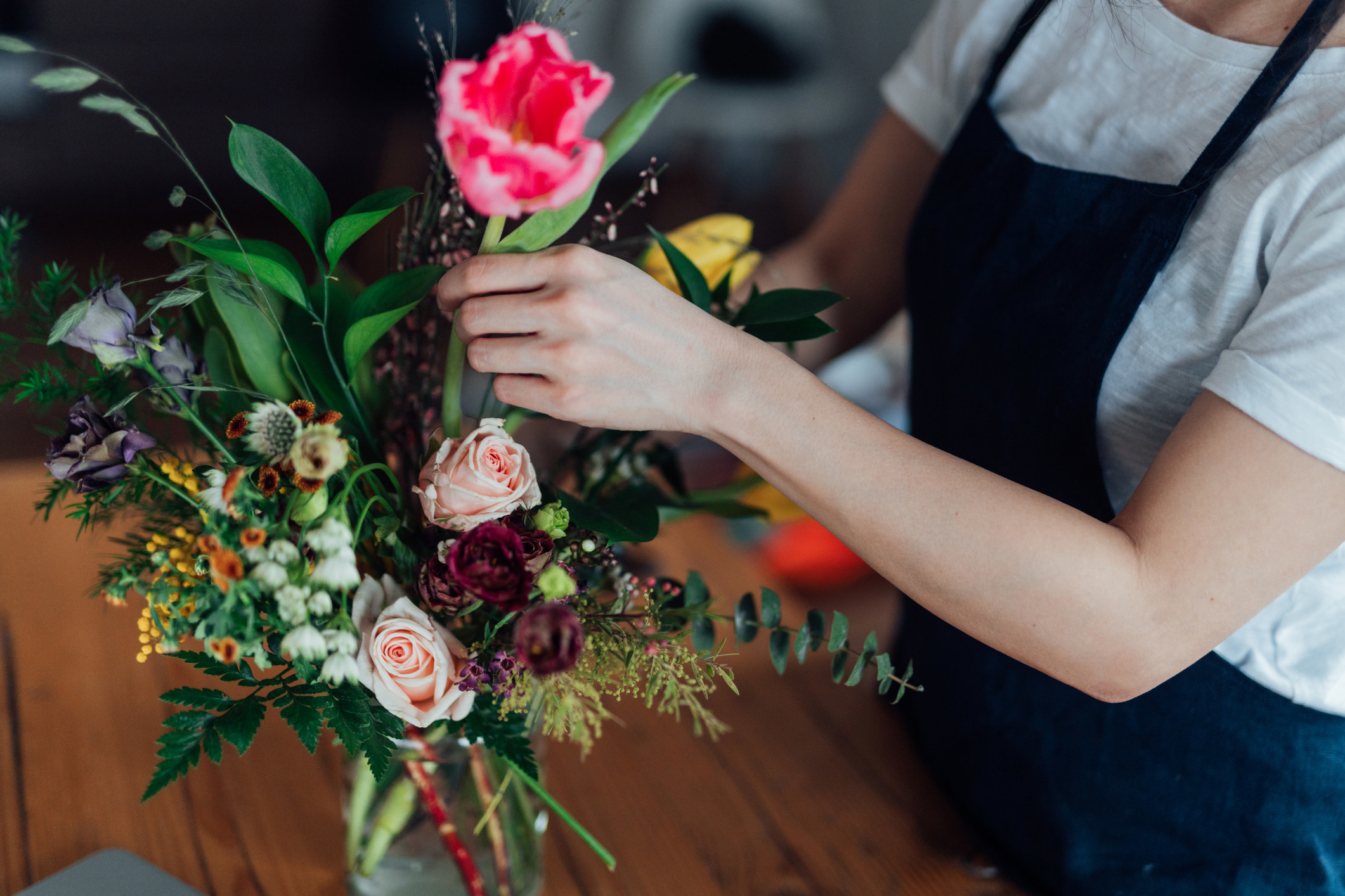 A person arranging flowers in a store