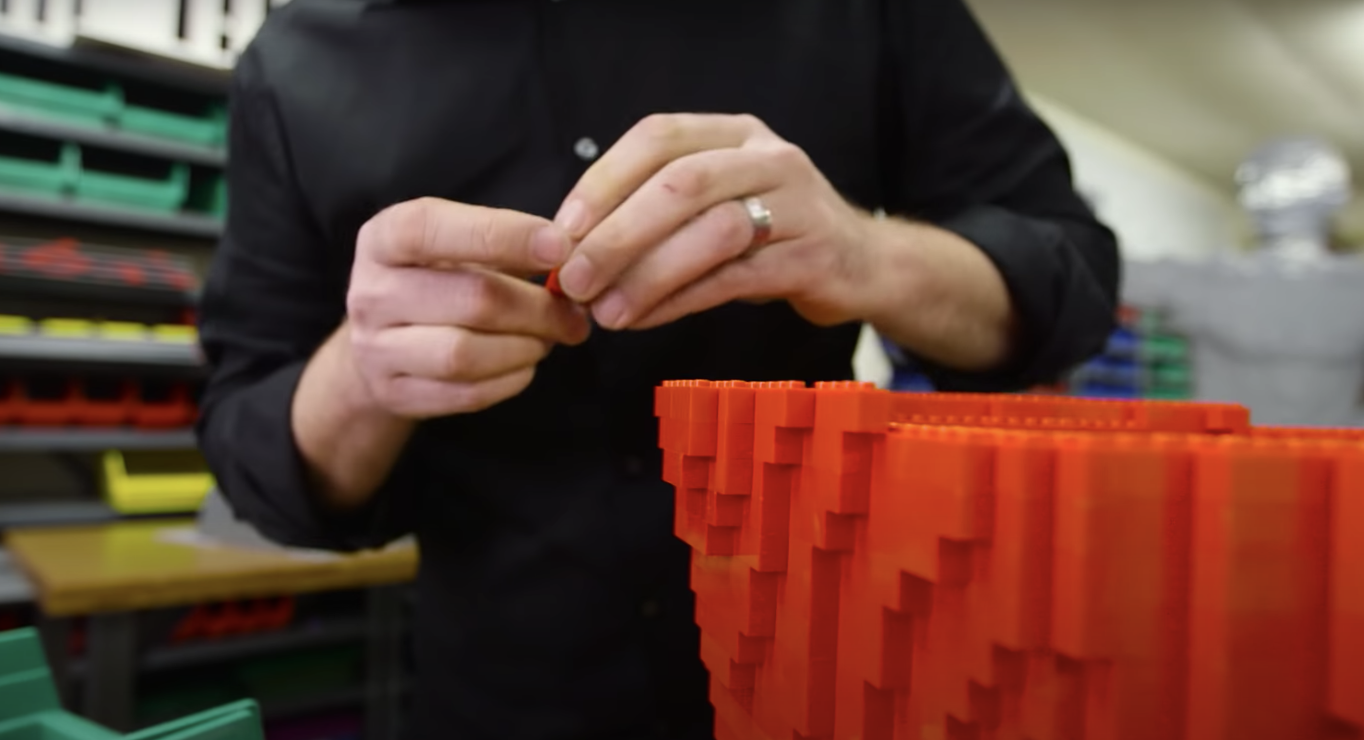 A person putting together a Lego structure