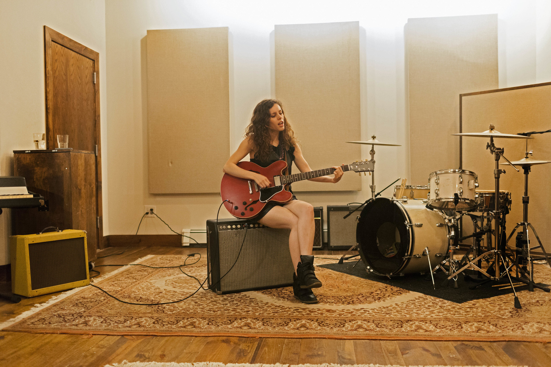 A person playing electric guitar in their studio next to a set of drums
