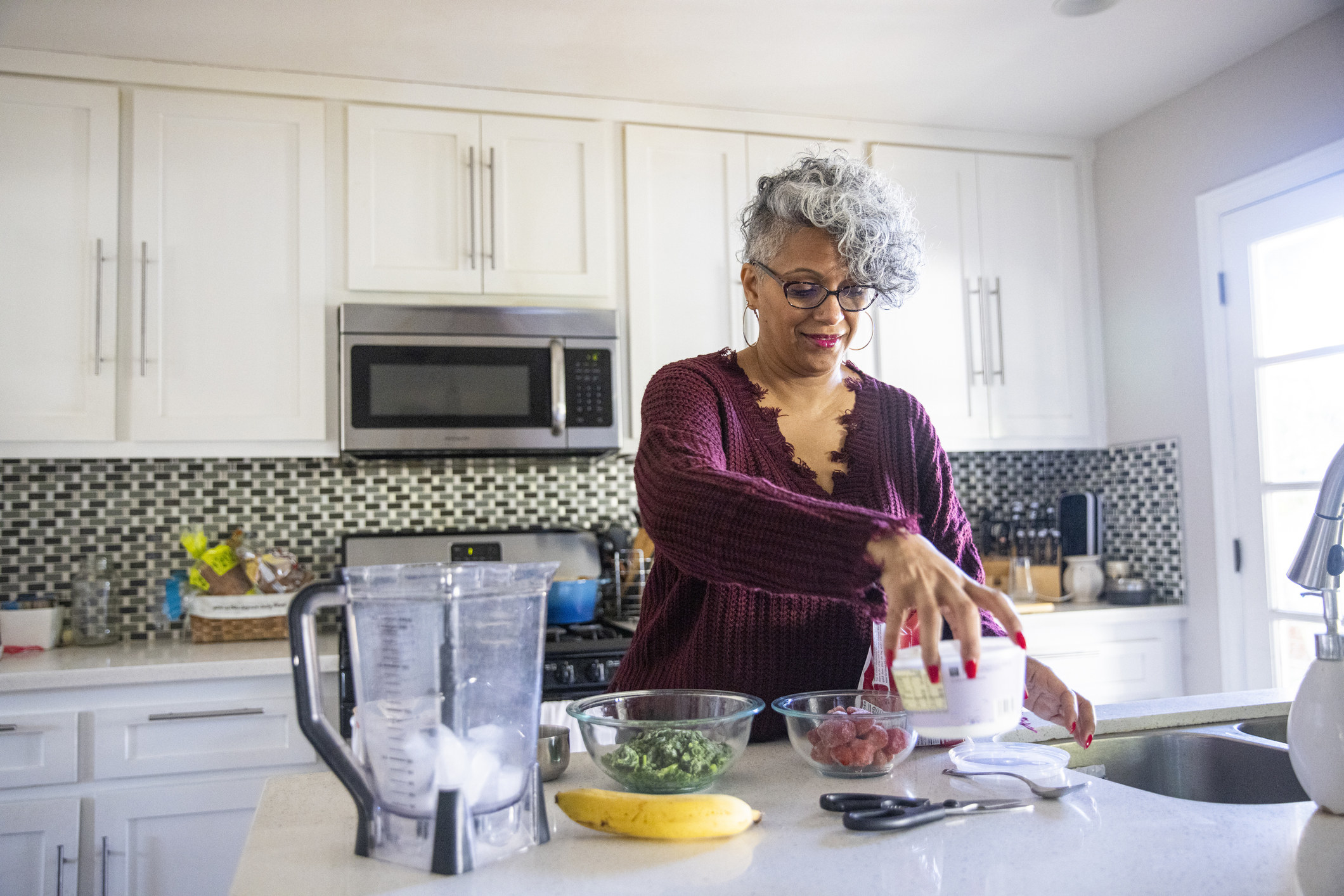 A woman organizing fruits and veggies on their countertop