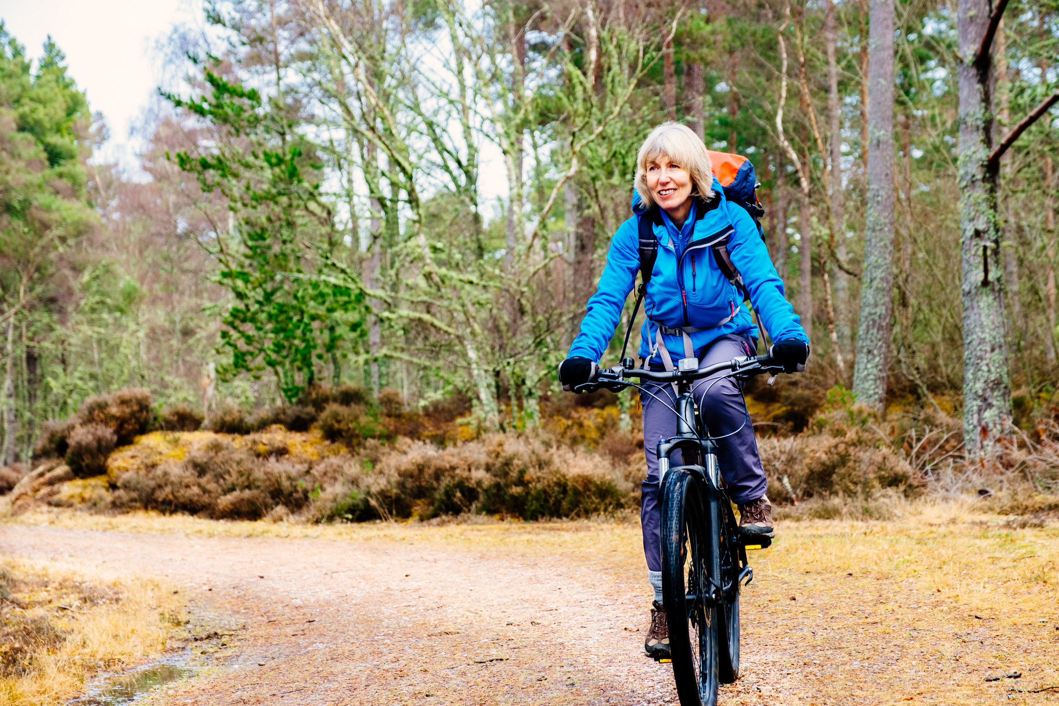 An older woman biking on a rural trail