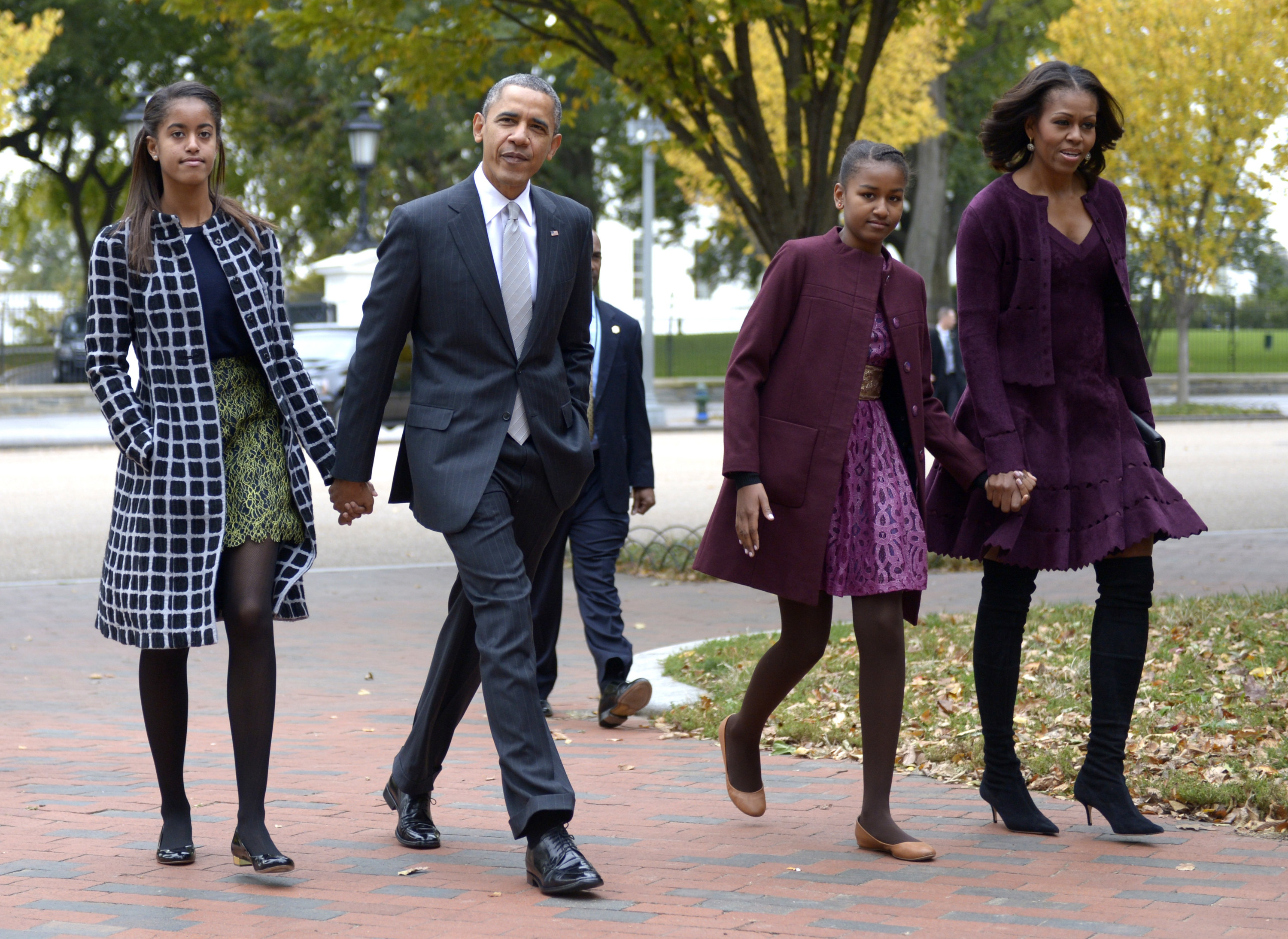 The Obama family holds hands while walking through a park