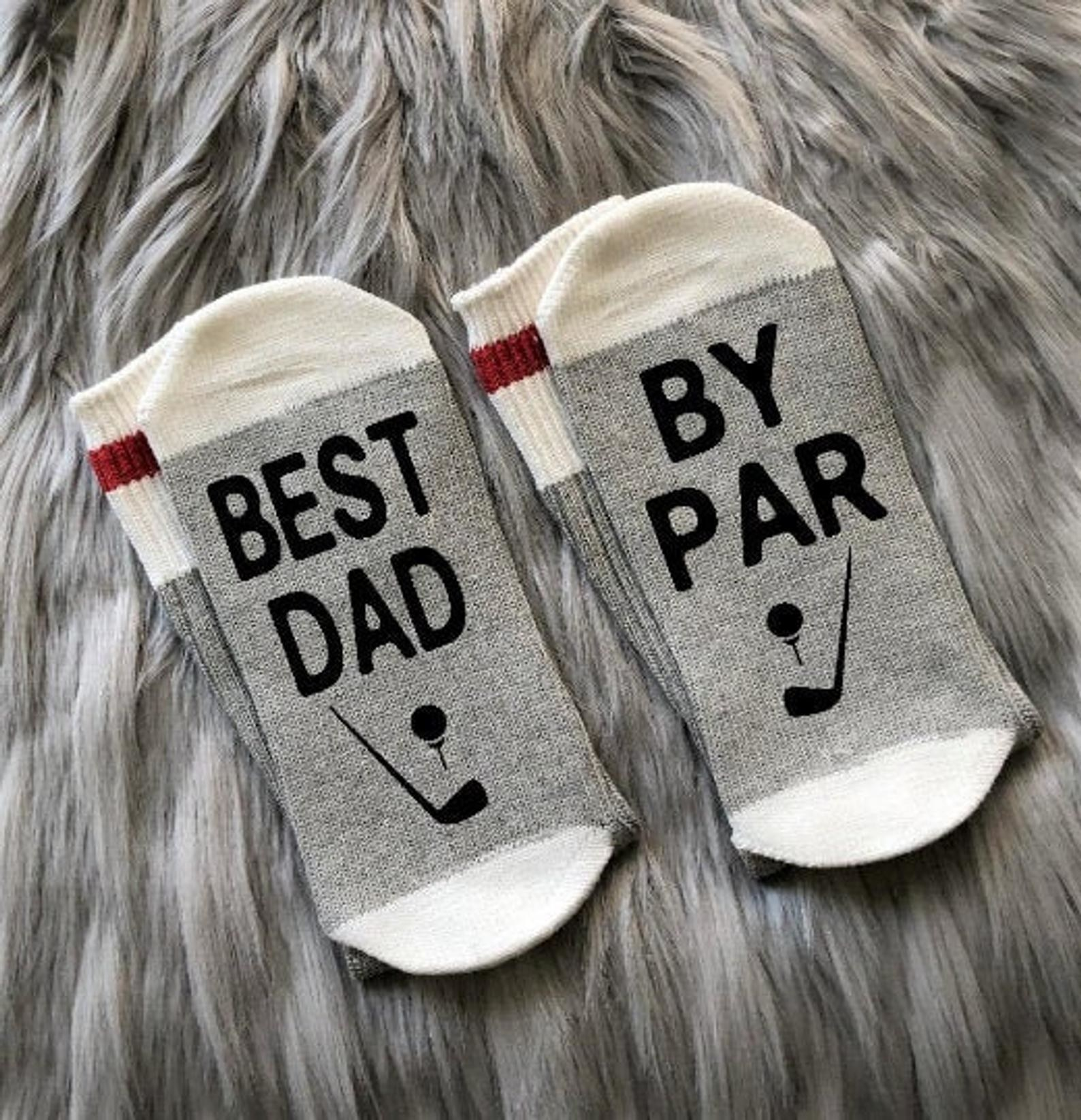 """Gray socks with white trim that have black lettering on the bottom, with one sock saying """"best dad"""" and the other saying """"by par"""""""