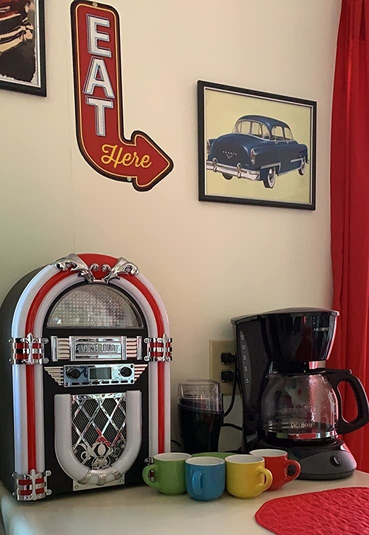 The jukebox sitting  on the counter in a 50's themed room