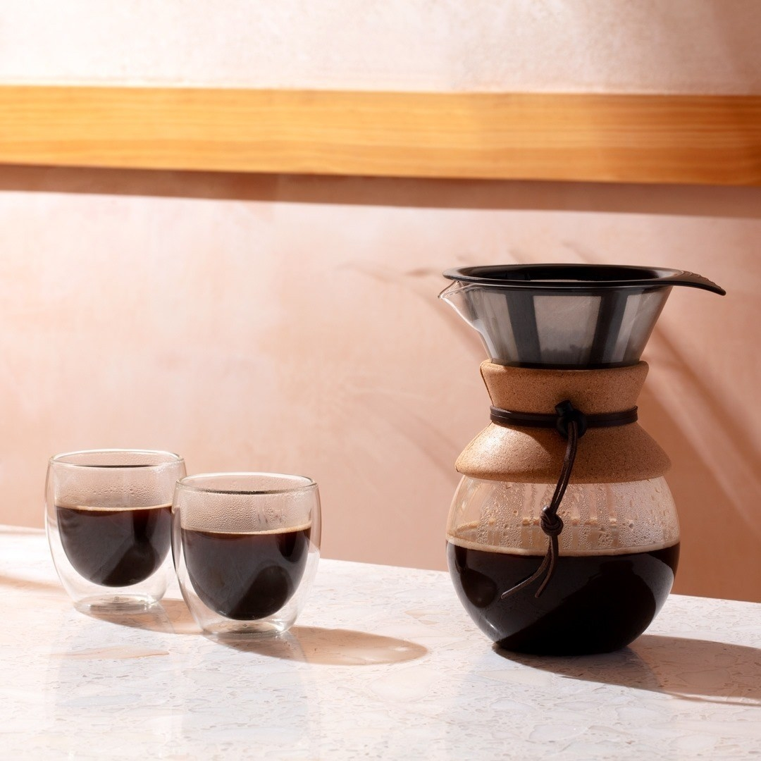 A pour over coffee maker and two small glass cups next to it