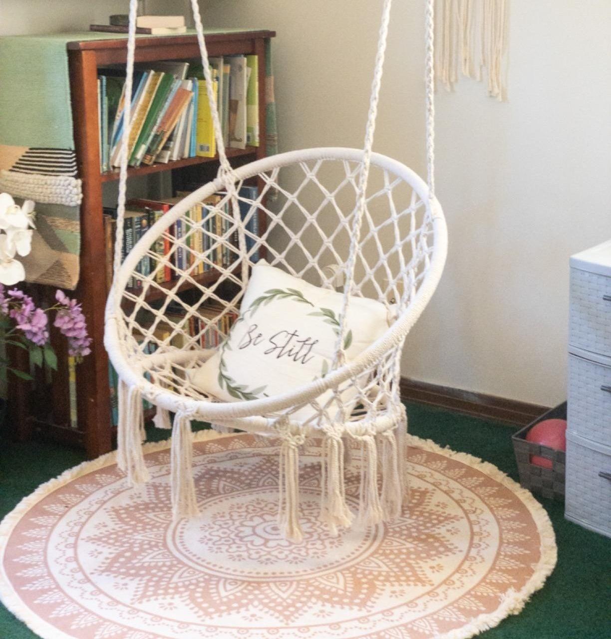 reviewer's white macrame hammock swing in their room