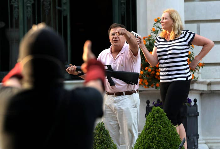 A man and woman, carrying a large gun and pistol, respectively, shout at protesters from a distance
