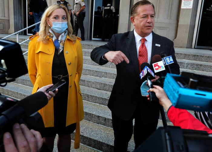 A man and woman speak into reporters' microphones outside a courthouse