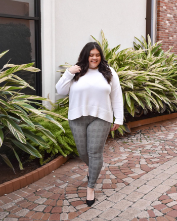reviewer wearing gray plaid leggings with white sweater and flats