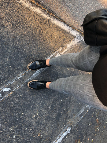 reviewer taking a photo from above and down towards legs showing the plaid gray print