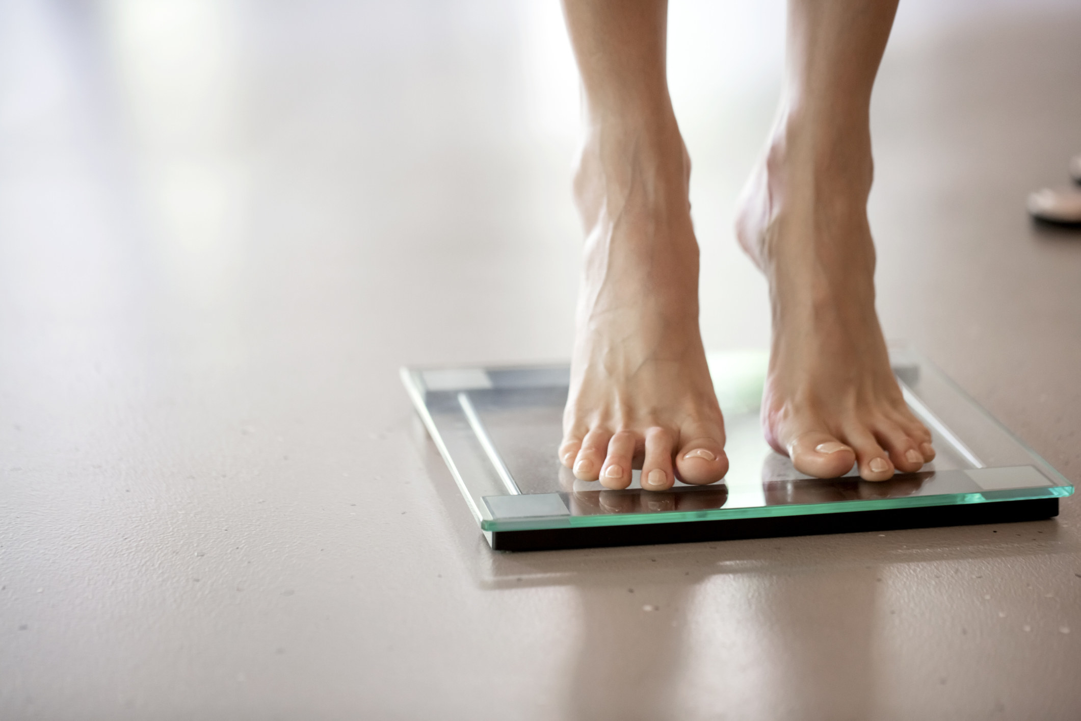A woman stepping on a scale.