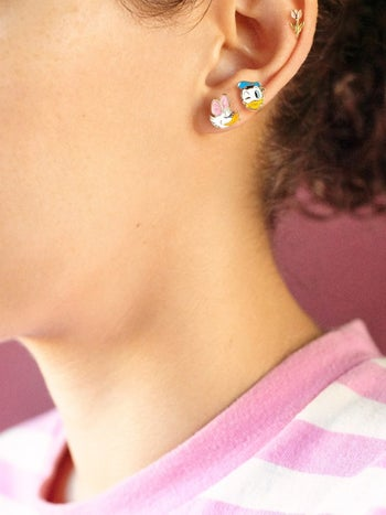 a model wearing the donald and daisy earrings