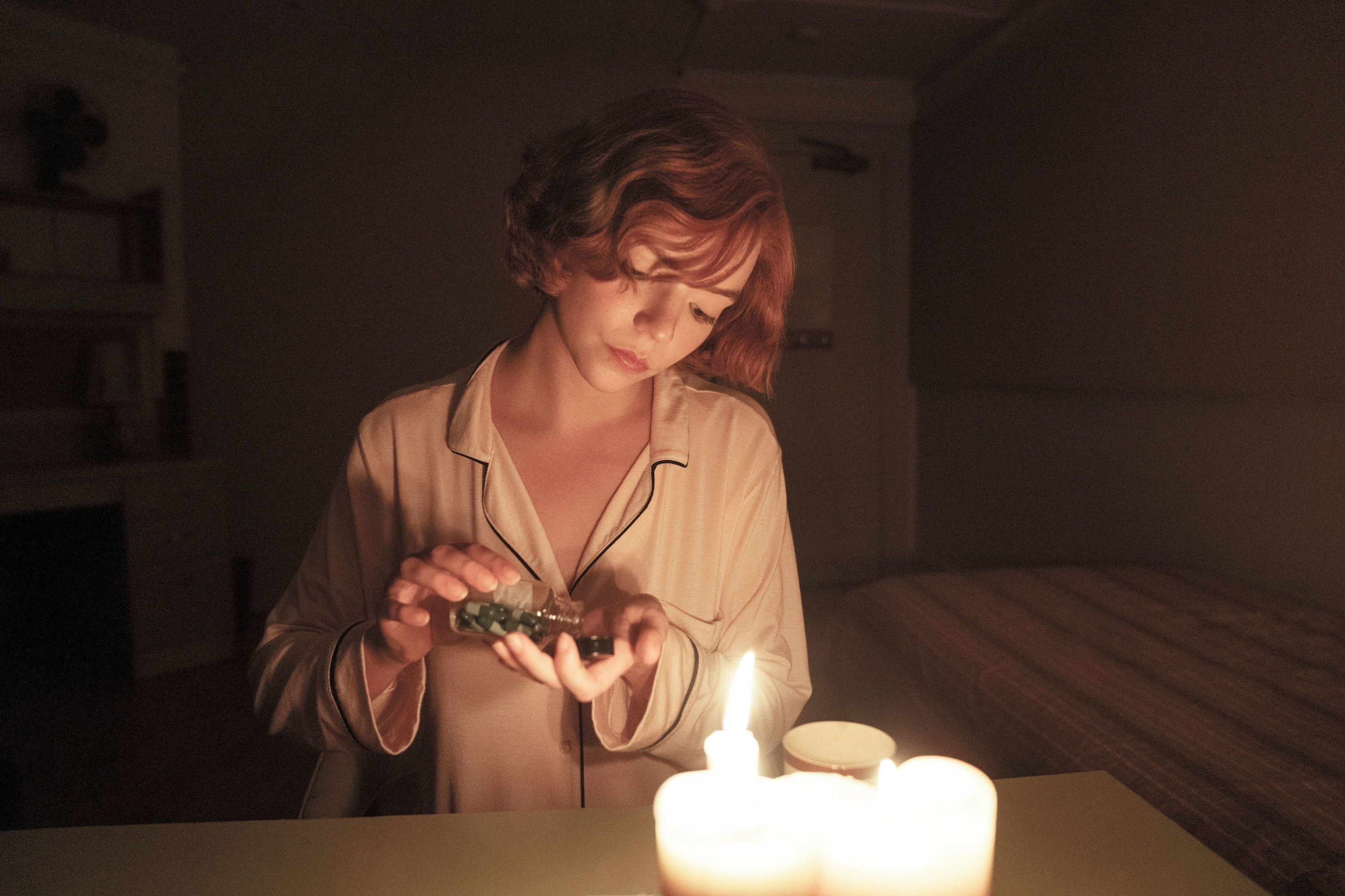 Woman taking some pills out of a bottle by candlelight