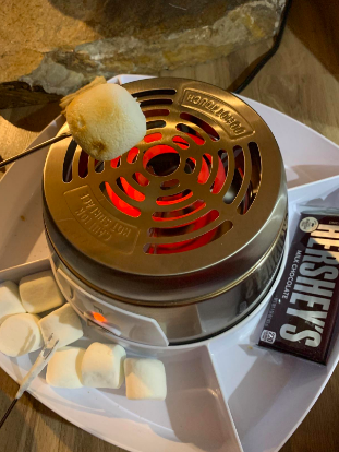 Reviewer roasting a marshmallow over the kit
