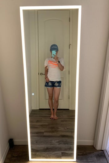 reviewer standing in front of their led-lighted mirror