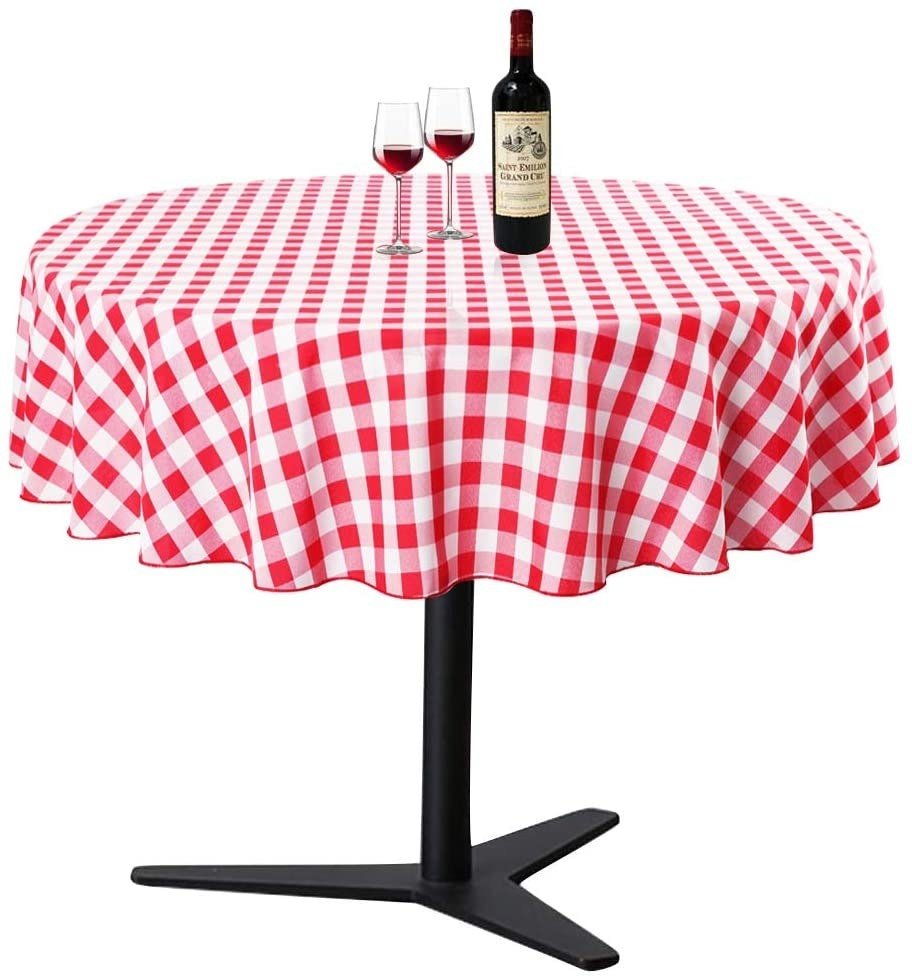 A table covered with the tablecloth and two glasses and a bottle of wine