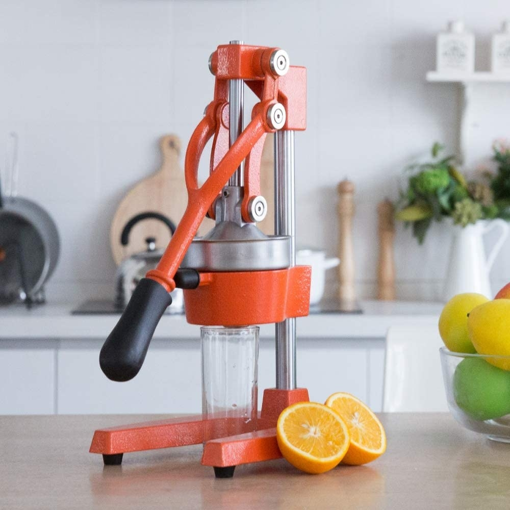 Hand press juicer with a cup underneath and orange halves beside it