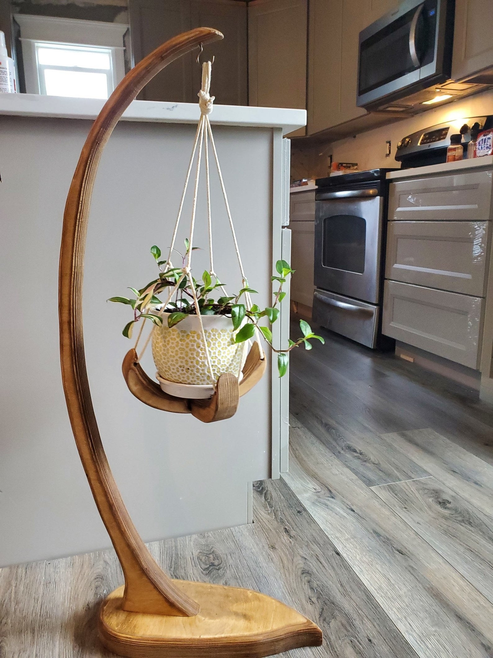 wooden plant stand that curves up and has a hanging vessel to put to put a plant in at the tip of the top