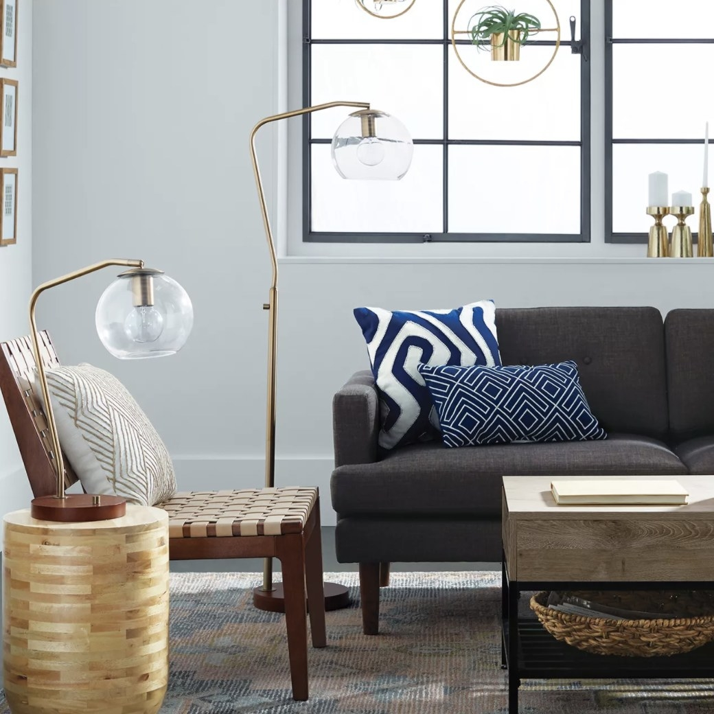 The lamp has a glass globe, circular bulb and curved gold stand