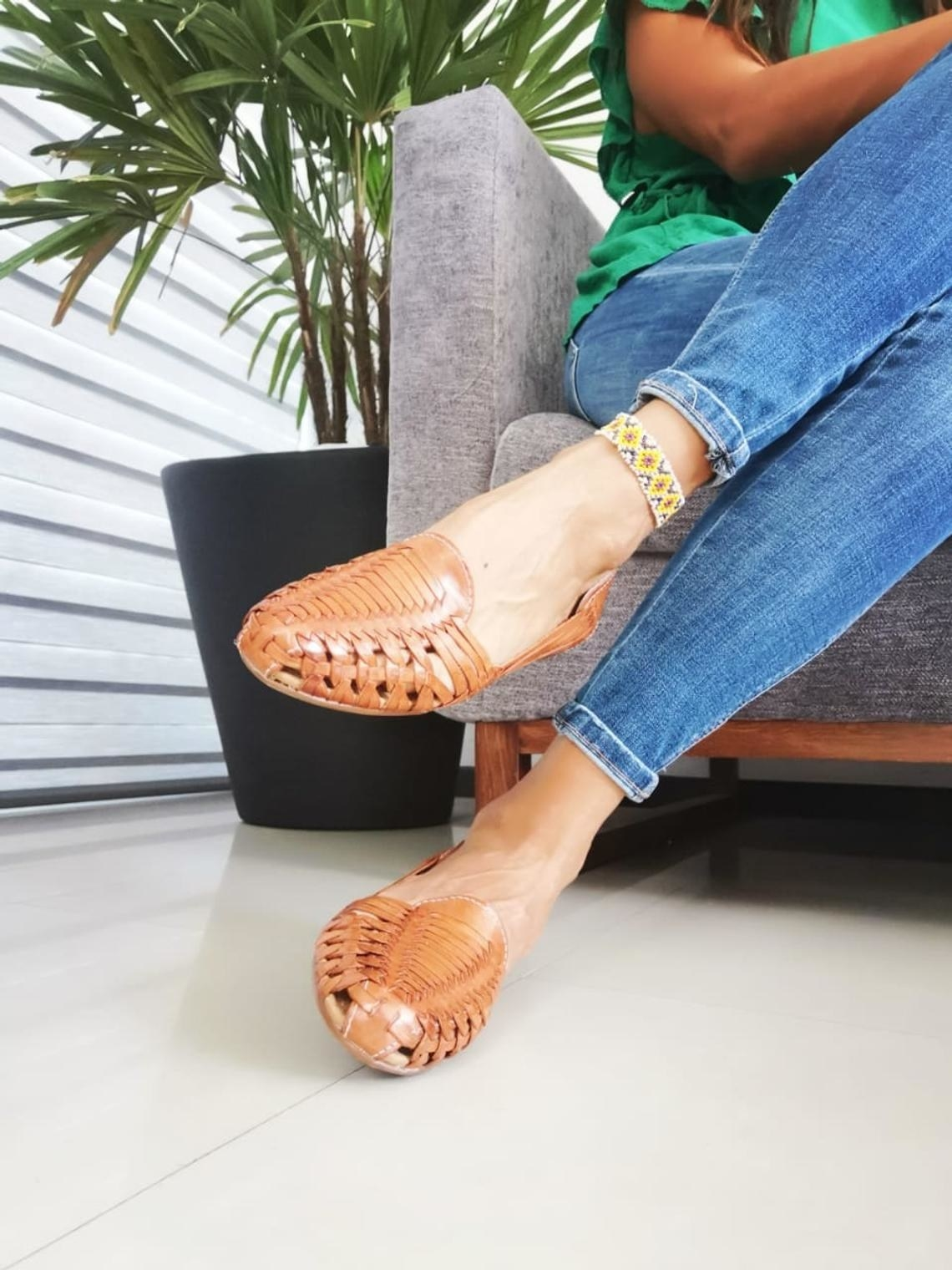 models feet in flat woven leather sandal/shoes with a light brown finish