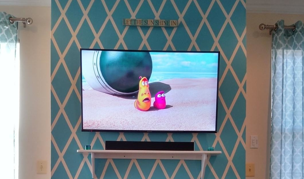 a reviewer photo with a television on the wall and the sound bar on the mantle