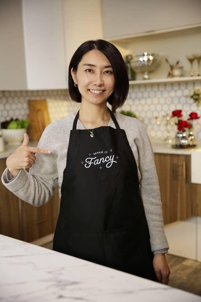 """Model wearing the black apron with logo """"Make it Fancy"""" on it"""