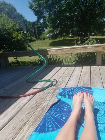 reviewer photo of a green mister outside by someone sunbathing