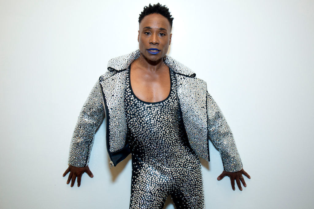 Billy posing in a sequined jumpsuit and matching jacket