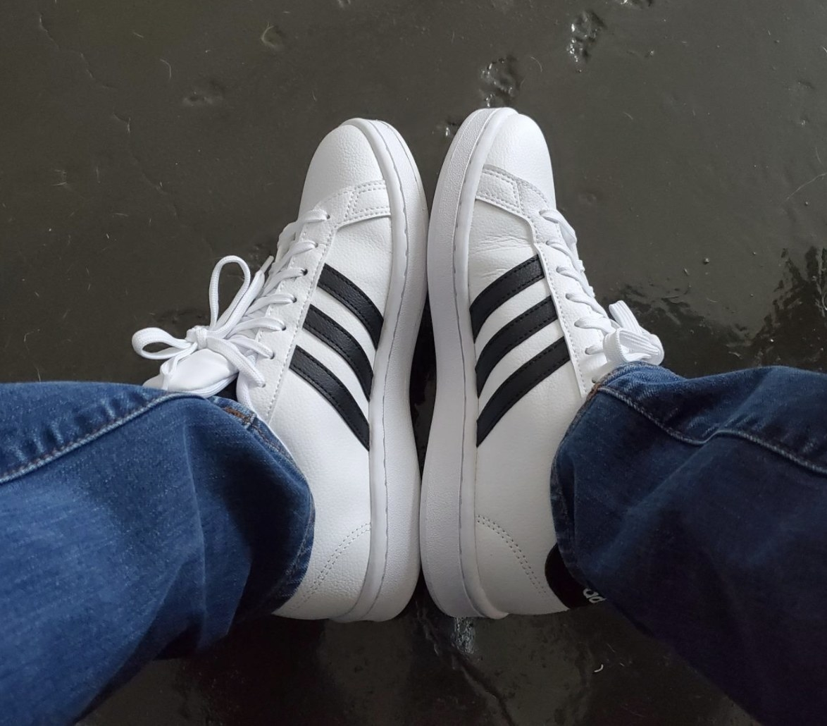 The white sneakers with three black stripes on the sides
