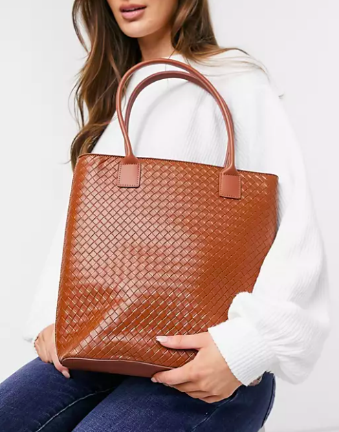 model holding brown woven tote
