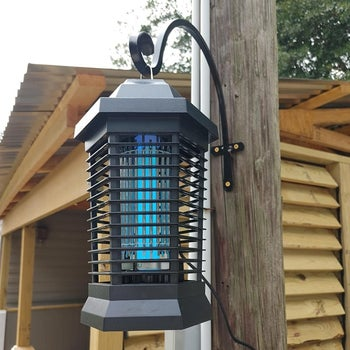 a reviewer photo of a bug zapper lantern hanging from a hook mounted on a post