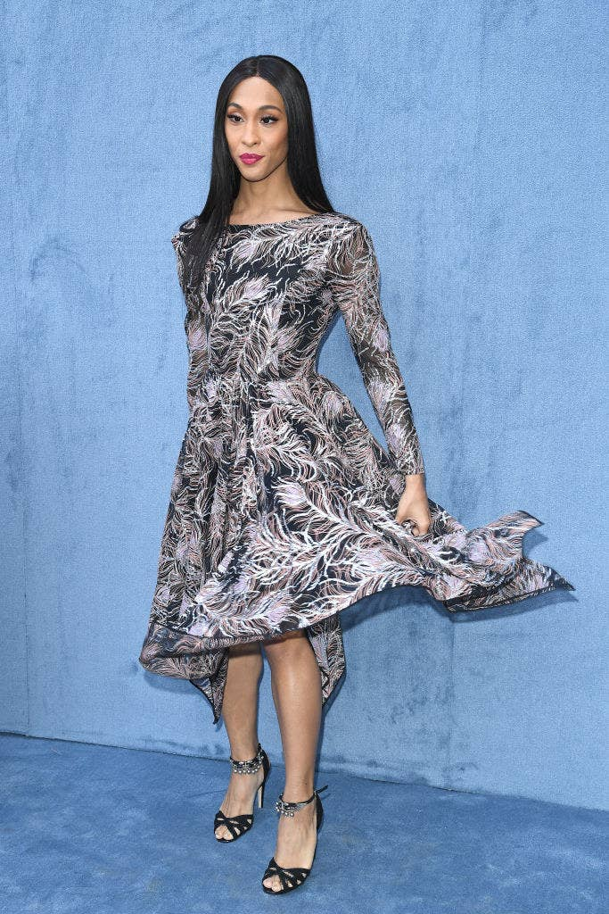 Mj Rodriguez wears a knee length dress that is being blown up by the wind.