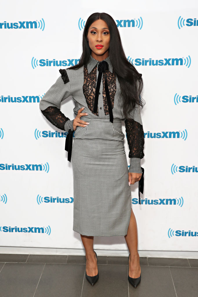 Mj Rodriguez wears a black and white tweed skirt. and blouse with black lace cut outs.