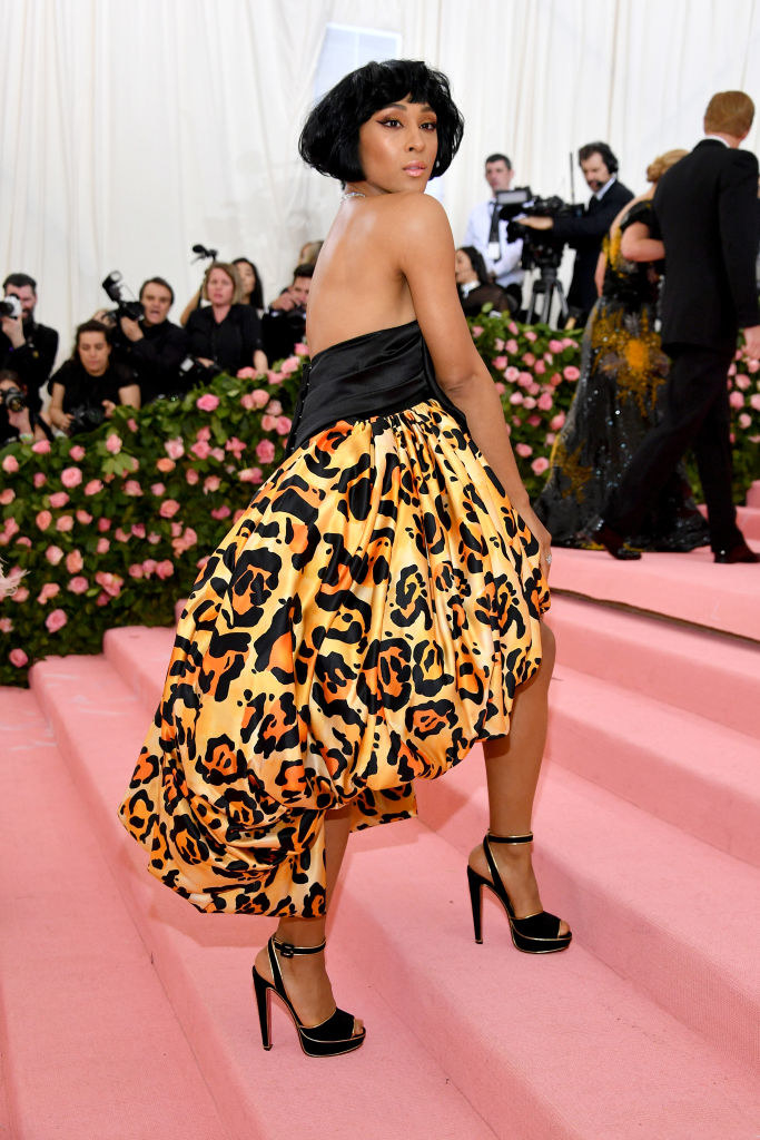 Mj Rodriguez wears a dress with a black bodice and poofy cheetah print skirt.