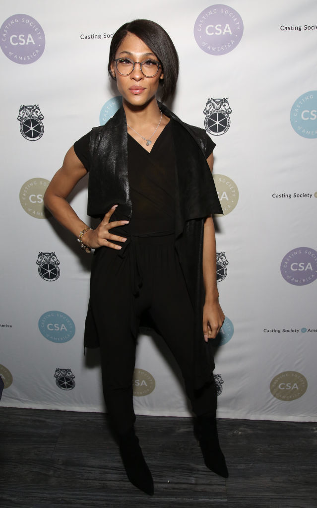 Mj Rodriguez wears an all black outfit and round framed glasses.