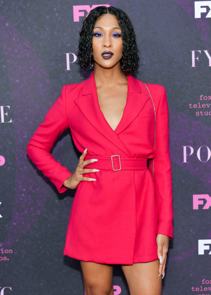 Mj Rodriguez wears a red short trench coat dress.