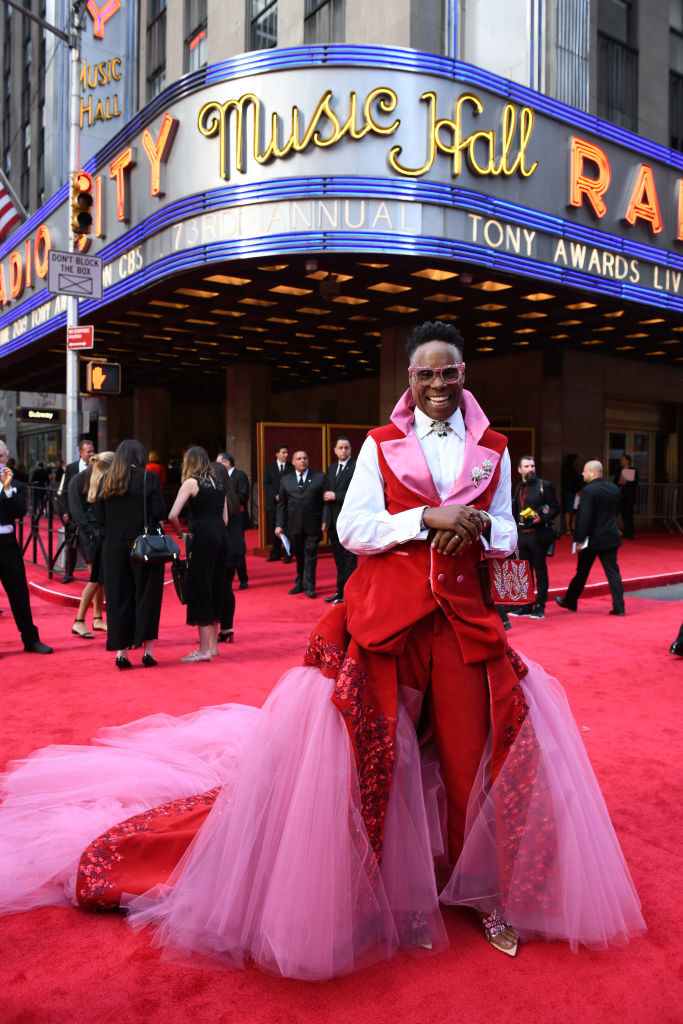 Billy Porter in front of Radio City in a pink and red suit with a tulle train
